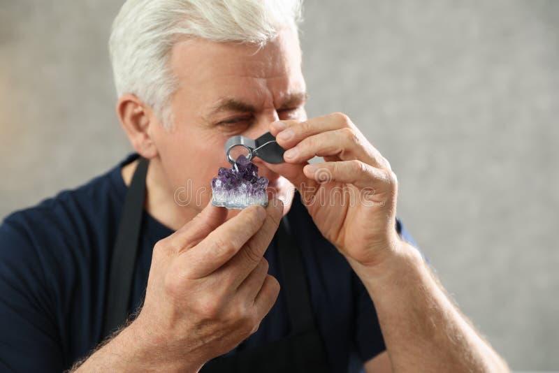 Male jeweler evaluating semi precious gemstone. In workshop stock image