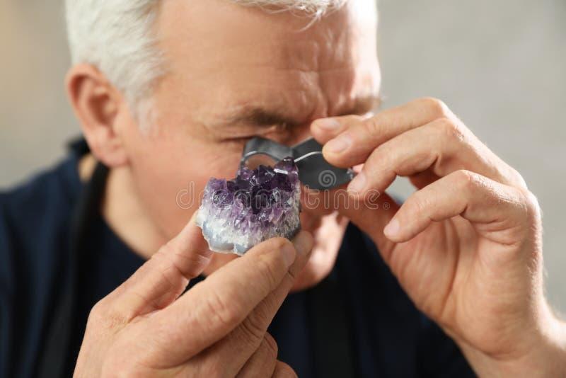 Male jeweler evaluating semi precious gemstone in workshop. Closeup royalty free stock image