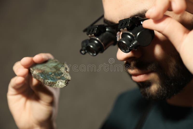 Male jeweler evaluating semi precious gemstone in workshop. Closeup royalty free stock images