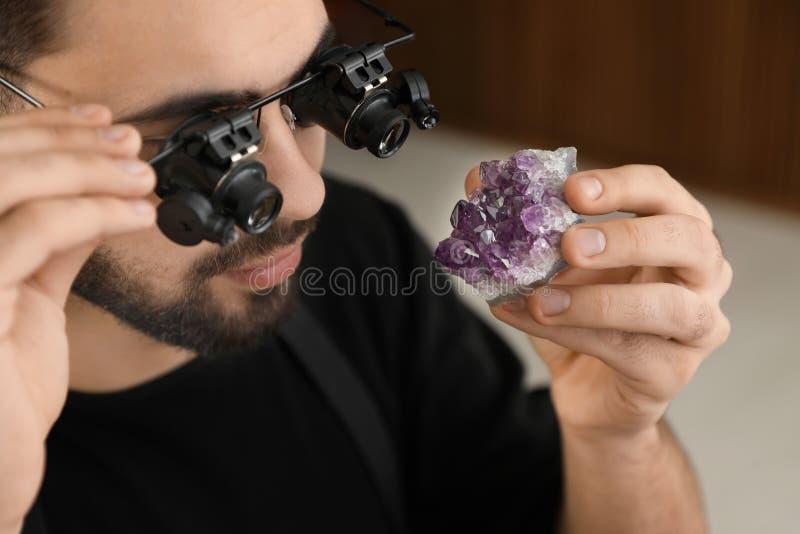 Male jeweler evaluating semi precious gemstone in workshop. Closeup stock image