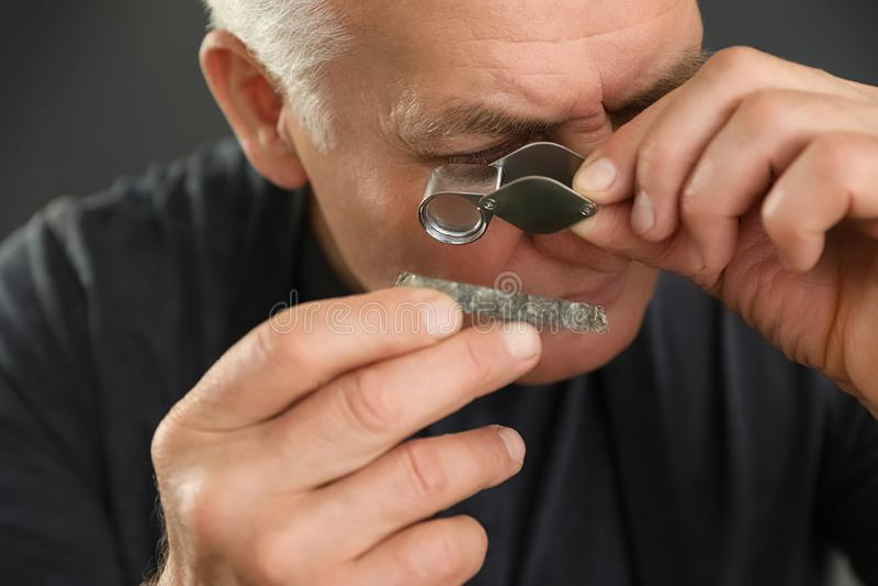 Male jeweler evaluating semi precious gemstone in workshop. Closeup stock photos