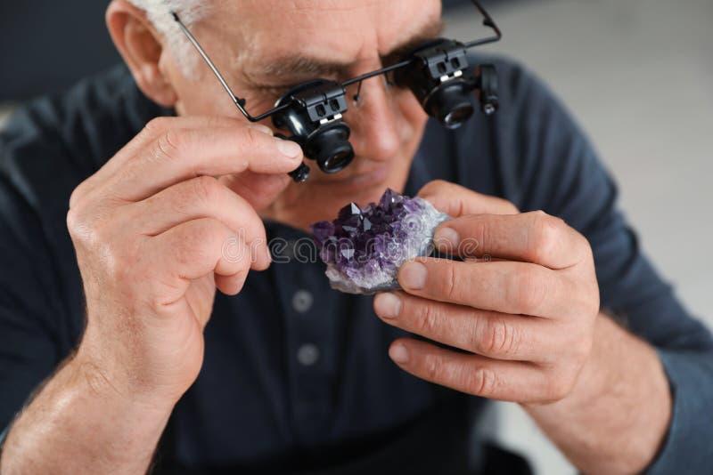 Male jeweler evaluating semi precious gemstone in workshop. Closeup royalty free stock photos