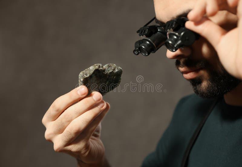 Male jeweler evaluating semi precious gemstone in workshop. Closeup stock photo