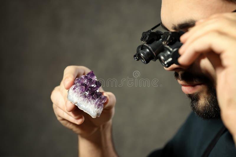 Male jeweler evaluating semi precious gemstone in workshop. Closeup royalty free stock photo