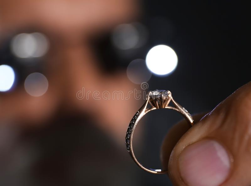 Male jeweler examining diamond ring in workshop stock photography