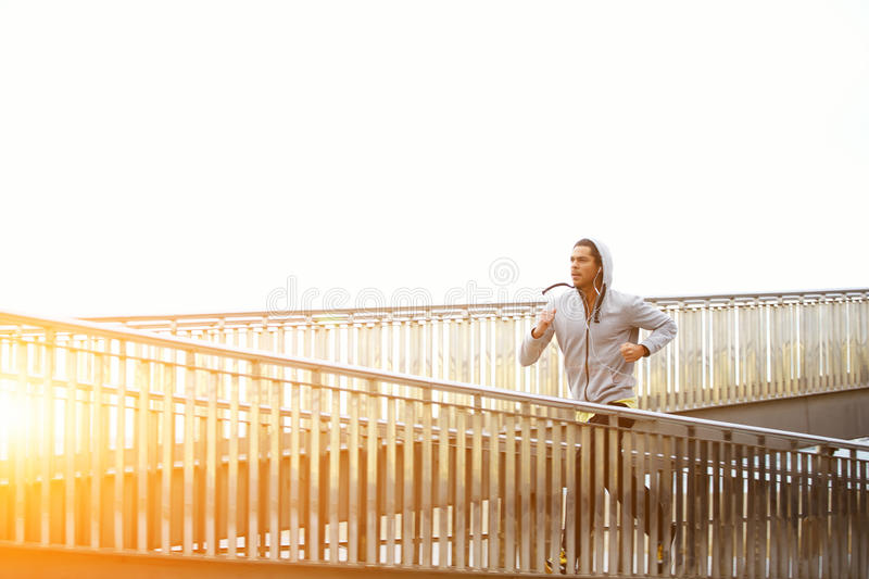 Male jogger exercising while listening to music with headphones stock photos