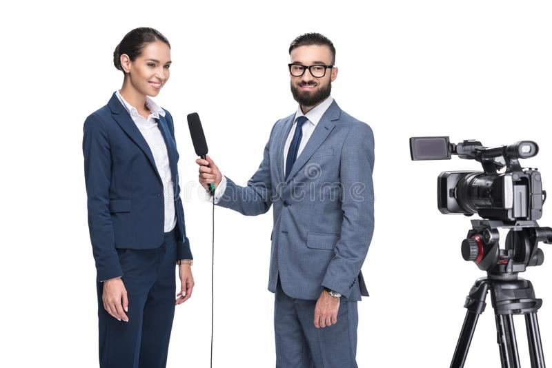 male journalist with microphone and video camera taking interview with businesswoman, royalty free stock photography
