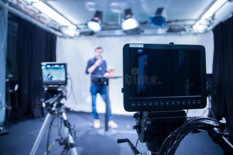 Journalist in a television studio is talking into a microphone, blurry film cameras royalty free stock photo