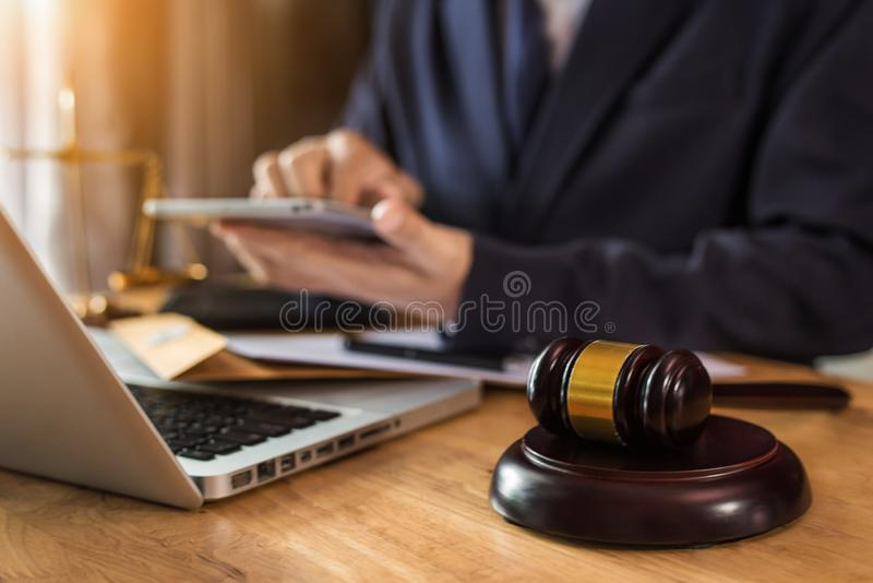 Male judge in a courtroom with the gavel working with digital tablet computer docking keyboard on wood table. stock photography