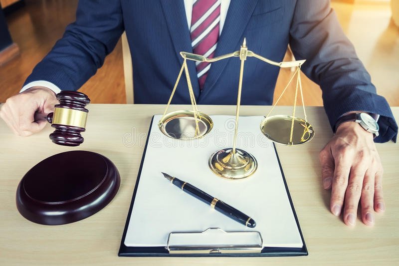 Male Judge In A Courtroom Striking The Gavel on sounding block royalty free stock photos