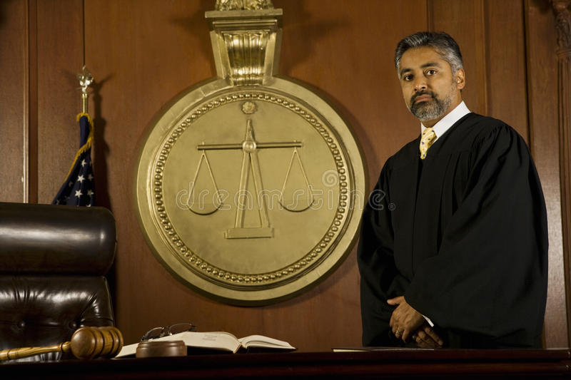 Male Judge Standing In Court Room. Portrait of middle age male judge standing in court room royalty free stock photos