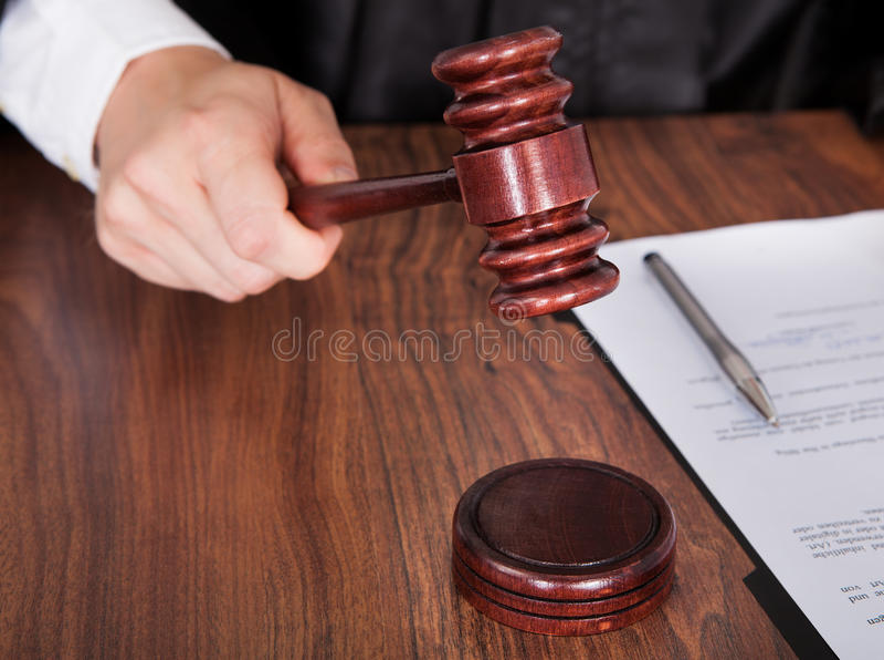 Male judge striking the gavel royalty free stock photo