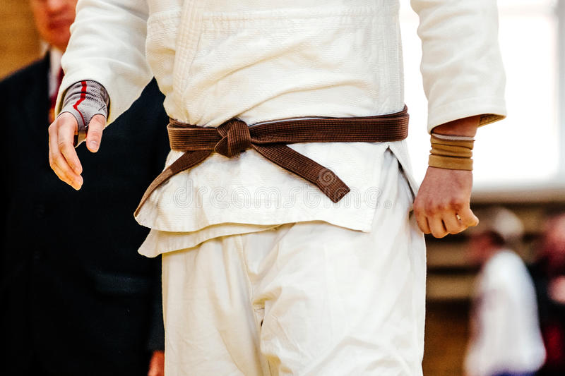 Male judo fighter. In white kimono with brown belt royalty free stock photo