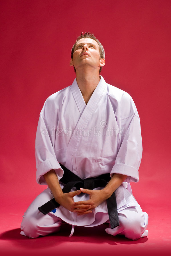 Male karate expert kneeling. A studio view of a black belt Karate expert in a white kimono, kneeling in front of a red black background, meditating stock photo