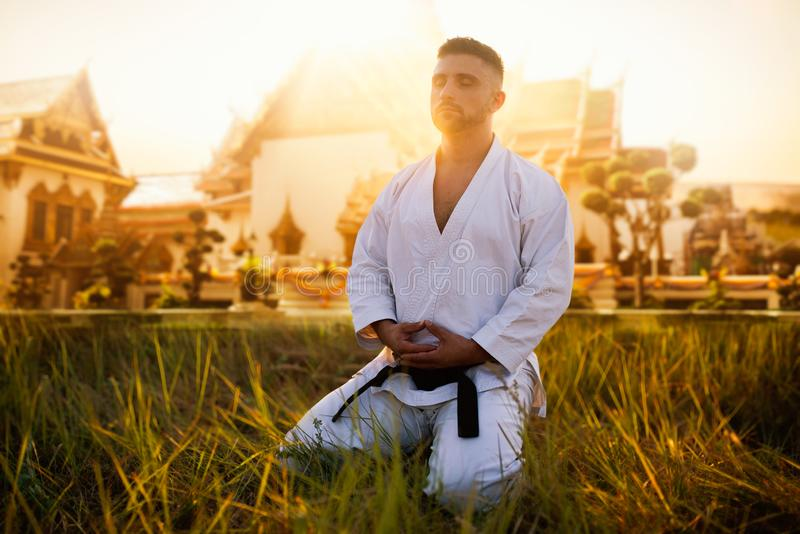 Male karate fighter against ancient temple. Male karate fighter sitting on the ground against ancient temple. Martial art training outdoor on sunset. Photo stock photography