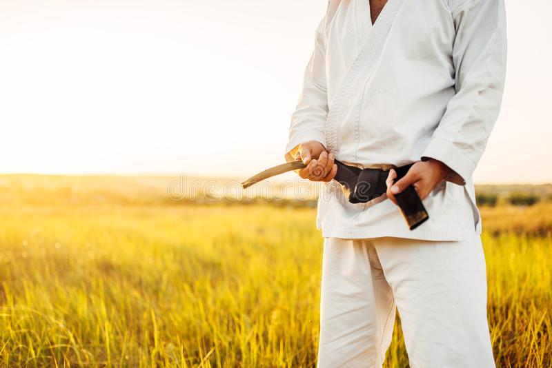 Male karate fighter in kimono with black belt. Male karate fighter in white kimono with black belt, summer field on background. Martial art training outdoor stock photography