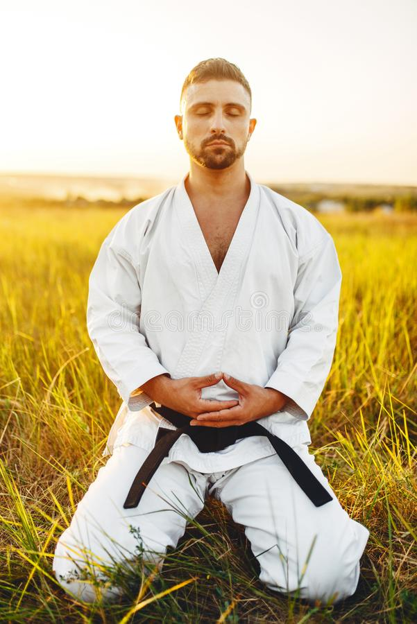 Male karate fighter sitting on the ground in field. Male karate fighter sitting on the ground in summer field. Martial art training outdoor royalty free stock photos