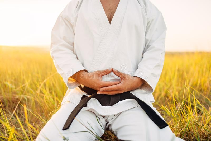 Male karate fighter sitting on the ground in field. Male karate fighter sitting on the ground in summer field. Martial art training outdoor stock image