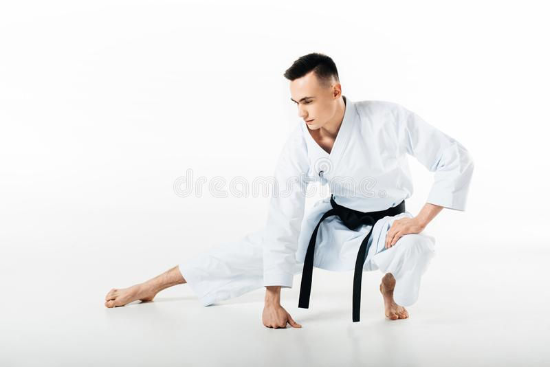 Male karate fighter stretching isolated. On white royalty free stock photos