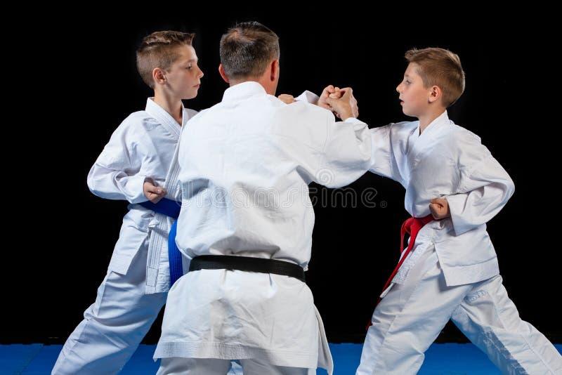 Male karate instructor training little children in dojo stock images
