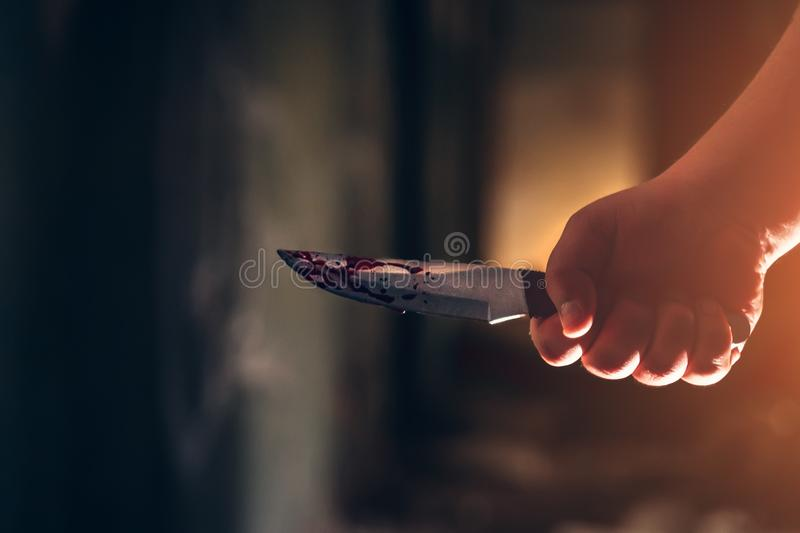 Male killer hand holding knife in blood in dark scary house royalty free stock images