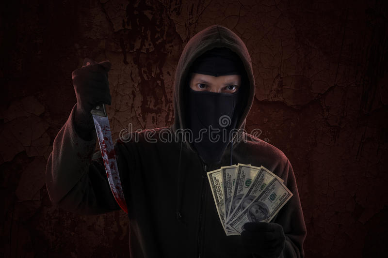 Male killer holds knife and money. Scary murderer showing bloody knife while holding money cash stock images