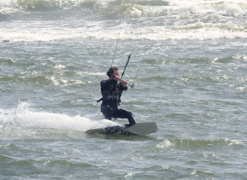 Recreational Water Sports Action. A Kiteboarder riding the waves. Dorset, UK. May 2018. stock images