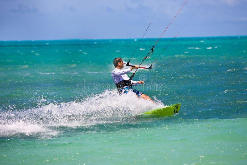 Male Kitesurfer turning hard. And slashing water stock images