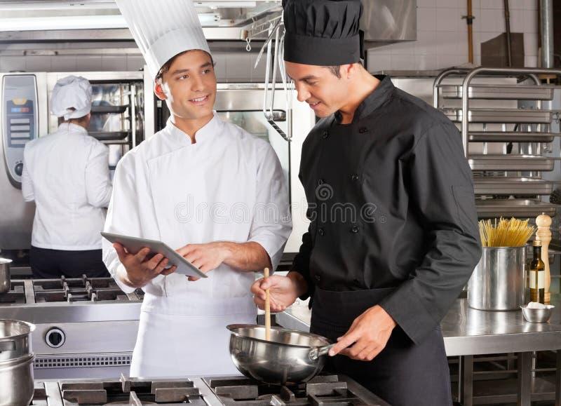 Male kock som hjälper kollegan, i att förbereda mat arkivbild