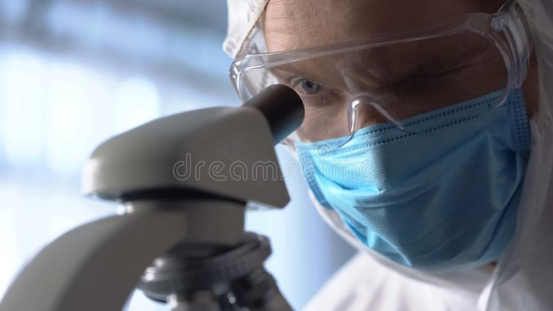 Male lab assistant in protective mask and eyewear using microscope for research royalty free stock photography