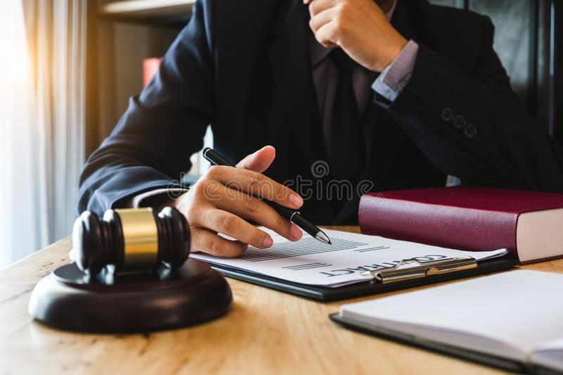Male lawyer in the office with brass scale. Justice and law concept.Male judge in a courtroom the gavel, working with smart phone and laptop and digital tablet royalty free stock image