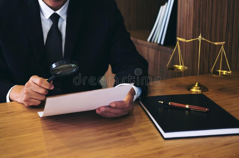 Male lawyer reading legal contract agreement and examining documents with magnifying glass in courtroom royalty free stock photo