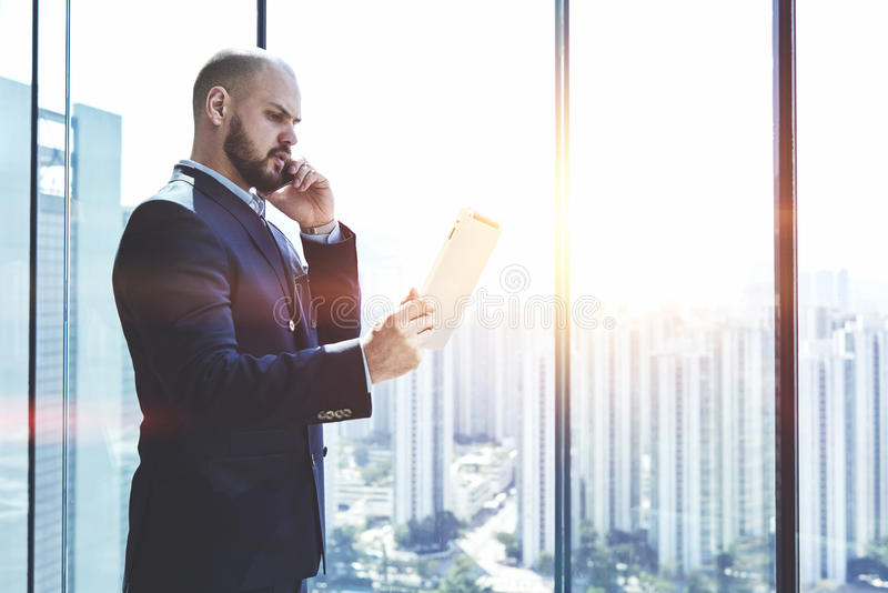Male lawyer is talking on mobile phone. Young man proud CEO is analyzing activity of the company via digital tablet and talking with financial manager during his royalty free stock photo