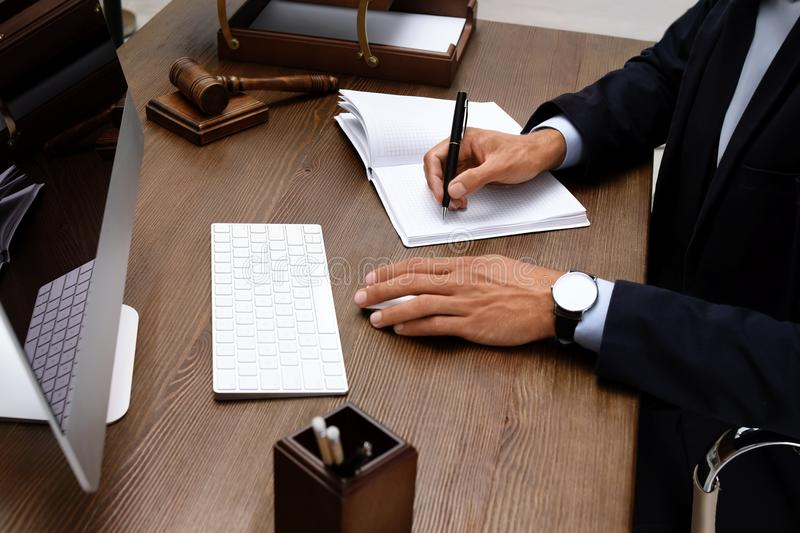 Male lawyer working with computer and notebook. At table, closeup stock photography