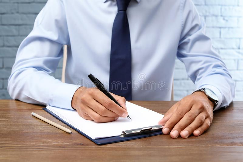 Male lawyer working with documents at table, closeup. Notary services stock photo