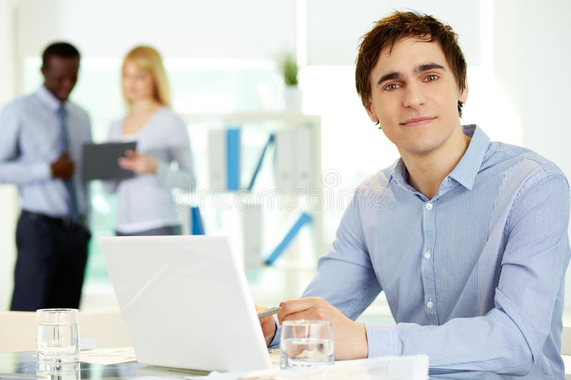 Male leader. Image of confident leader with laptop looking at camera from workplace stock photography