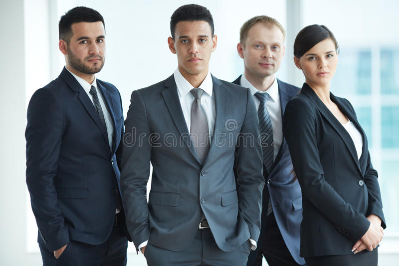 Male leader. Portrait of confident business partners looking at camera with male leader in front stock photo