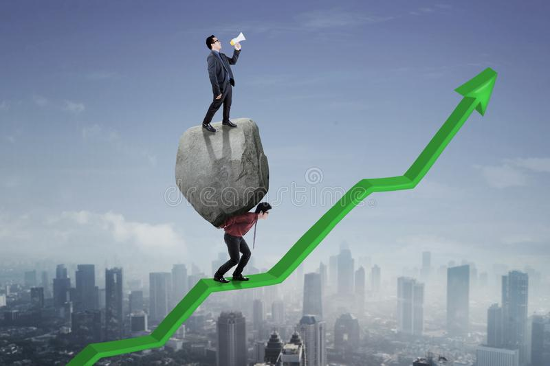 Male leader and his employee on upward arrow. Male leader standing on a stone while commanding his employee with a megaphone to walk on an upward arrow stock photos