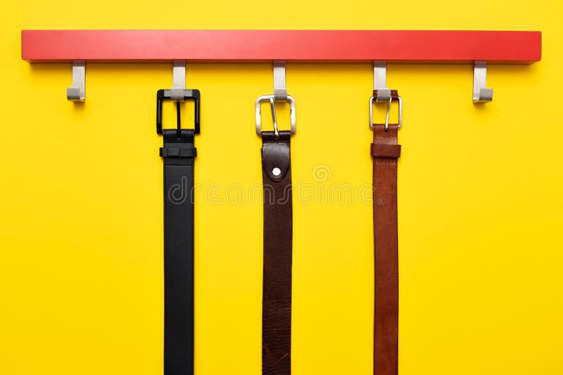 Male leather belt on hanger on yellow background royalty free stock photos