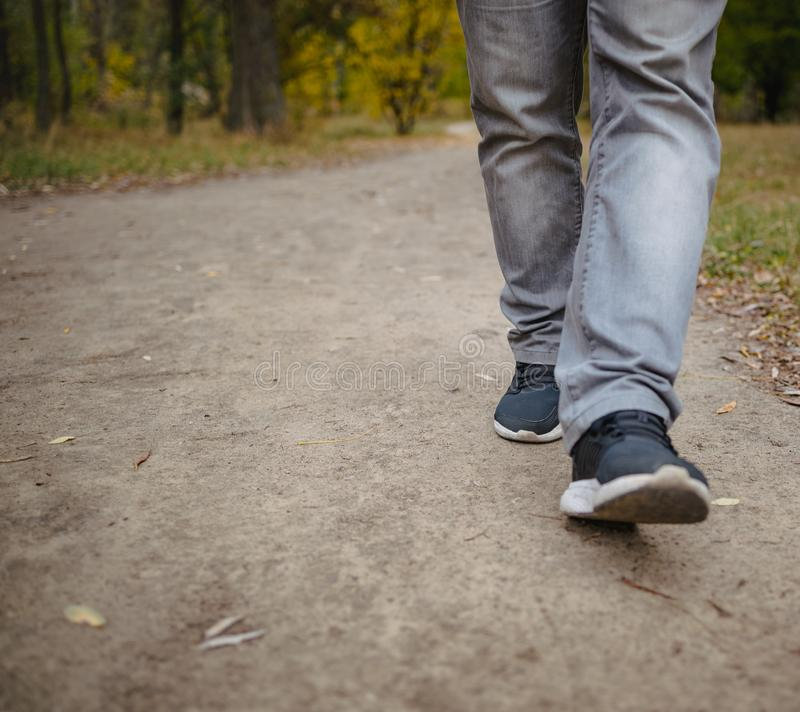 Male legs in jeans and sneakers walking out into the distance on the ground covered with fallen yellow leaves. Autumn arrival royalty free stock images