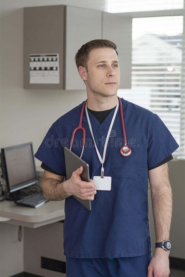 Male looking out window smiling while holding tablet for medical information stock images