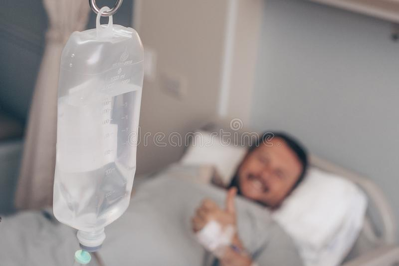 Male lying on a hospital bed. Dropper in a man`s hand in a hospital. royalty free stock photos