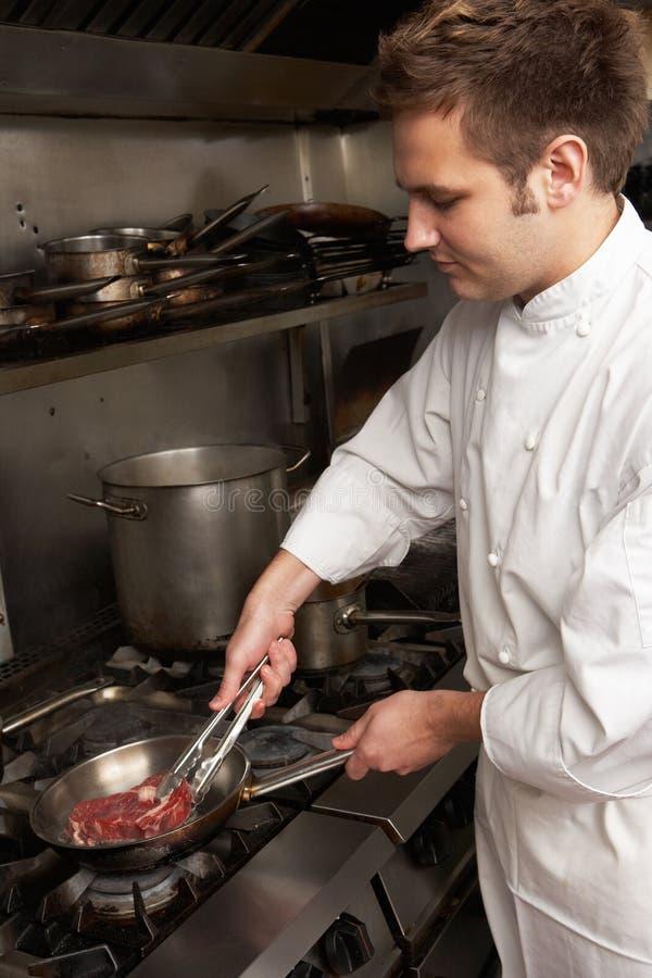 male mål för kockspis som förbereder restaurangen royaltyfria bilder