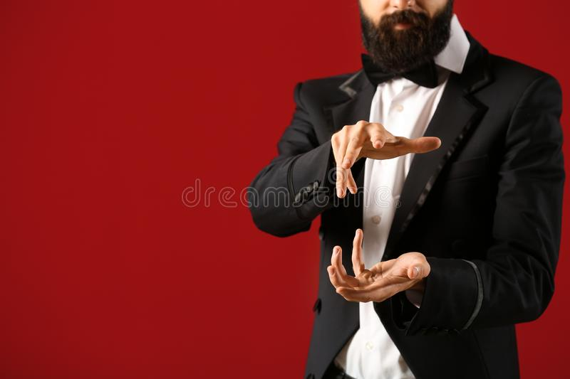 Male magician on color background royalty free stock photos