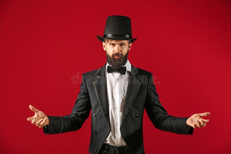 Male magician on color background royalty free stock photography
