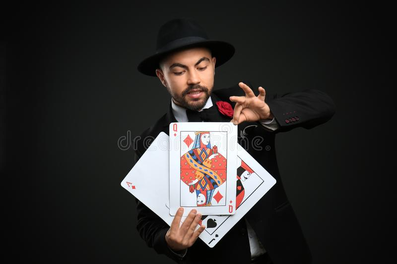 Male magician showing tricks with cards on dark background stock photography