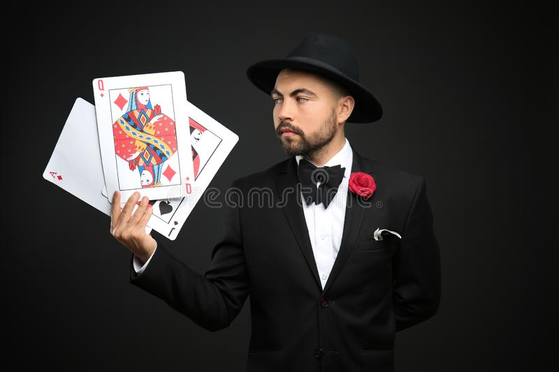 Male magician showing tricks with cards on dark background royalty free stock images