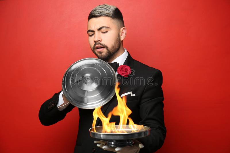 Male magician showing tricks on color background stock photography