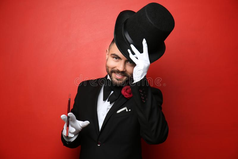 Male magician showing tricks on color background stock photos