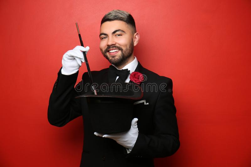 Male magician showing tricks with hat on color background stock photo